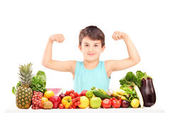 Healthy child showing his muscles and sitting on a table full of Royalty Free Stock Photography
