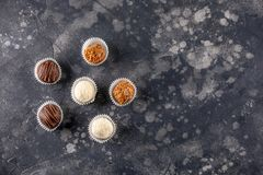 Healthy chocolate and coconut truffles with nuts and dates. In a dark background royalty free stock photo
