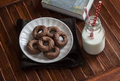 Healthy chocolate cookies, bottle of milk and a book on a brown wooden surface. Stock Photo
