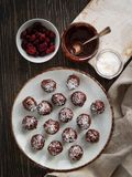 Healthy chocolate truffles with nuts, dates, dried cranberries and coconut flakes on rustic Background. Top view with copy space stock photo