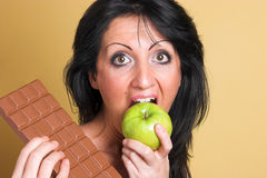 Healthy choice. Woman choosing a apple over chocolate Stock Photography