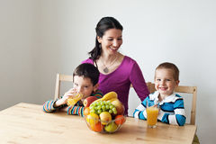 Healthy choice - healthy breakfast. Children sitting at the table with their mother and drinking orange juice Stock Images