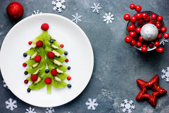 Healthy Christmas dessert snack breakfast for kids - kiwi blueberry raspberry Christmas tree. Top view stock photography