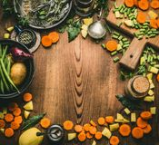 Healthy clean cooking and eating concept. Kitchen table from above with various ingredients: chopped vegetables, herbs and spices,. Cutting board and spoon Royalty Free Stock Image