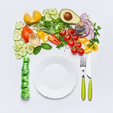 Healthy clean eating or diet food concept. Various salad vegetables with white plate , cutlery and green measuring tape. On white background, top view, flat lay royalty free stock image