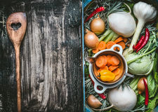 Healthy clean food background with various organic fresh vegetables in a crate and wooden cooking spoon with heart on dark rustic Royalty Free Stock Images