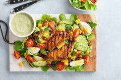 Cobb salad with chicken, avocado, tomato, eggs and corn stock images