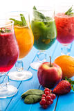 Healthy colorful smoothies with fresh fruits on wooden background. Detox and diet food concept and background Royalty Free Stock Images