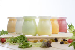 Healthy coloured yogurts with fruits and nuts. Front facing bottles of coloured yogurt on the table with fruits, nuts and salad scattered around Royalty Free Stock Photo