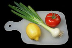 Healthy colours. Tomato ,onion and lemon on table Stock Photo