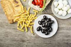 Healthy comfort food: ingredients for cooking pasta, salads, olives, sweet onions, mozzarella cheese, olive oil, juicy Royalty Free Stock Photos