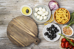 Healthy comfort food: ingredients for cooking pasta, salads, olives, sweet onions, mozzarella cheese, olive oil, juicy Royalty Free Stock Photo
