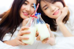Healthy concept. Attractive beautiful women is celebrating anniversary of their friendship by drinking fresh milk instead alcohol. Ic beverages. Pretty girls stock photography