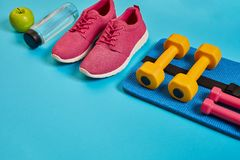 Healthy concept, diet plan with sport shoes and bottle of water and dumbbells on blue background, healthy food and Royalty Free Stock Photos