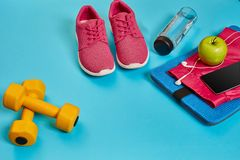 Healthy concept, diet plan with sport shoes and bottle of water and dumbbells on blue background, healthy food and. Exercise concept. Top view. Copy space Stock Photos