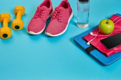 Healthy concept, diet plan with sport shoes and bottle of water and dumbbells on blue background, healthy food and royalty free stock image