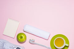 Healthy concept. Sneakers, tea, apple and measure tape on pastel Royalty Free Stock Images