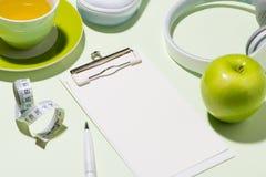 Healthy concept. Sneakers, tea , apple on pastel color backgroun Stock Photos
