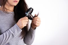 Healthy concept. Woman looking through a magnifying glass ends of her damaged long loss hair stock image