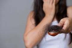 Healthy concept. Woman show her brush with long loss hair and looking at her hair royalty free stock image
