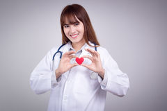 Healthy concept : Young Asian doctor with red heart in hand. Stock Photos