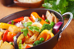 Healthy Cooked Main Dish on a Pan with Herbs. Close up Healthy Cooked Main Dish with Veggies and Spices on a Black Pan with Herbs, Placed on Wooden Table Royalty Free Stock Photos