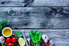 Healthy cooking concept. Close up of rustic wooden background with raw various vegetables and seasoning cooking ingredients on old kitchen table, top view, place royalty free stock photos