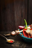 Healthy cooking with fresh organic vegetables and oil. Scene on rustic kitchen table over wooden background. Stock Photos