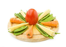 Healthy cooking with fresh vegetables. Baby carrots, corn, beans and tomato on wooden chopping board. Isolated over white stock photography