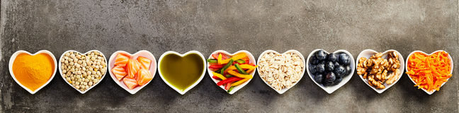 Healthy cooking ingredients banner concept. Healthy cooking ingredients placed in long straight row of small heart-shaped bowls, studio shot from above over grey Stock Images