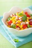 Healthy corn salad with tomato onion white bean basil Stock Photos
