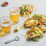Healthy corn tortillas with beer in glasses over light background Royalty Free Stock Photo