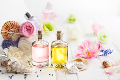 Healthy cosmetic care. Bottles with essential aroma oil,towels different colors and fresh flowers  on white wooden background. Spa concept. Healthy cosmetic Royalty Free Stock Images