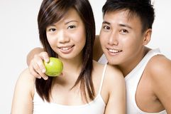 Healthy Couple 2. A healthy-looking asian couple in white with an apple Royalty Free Stock Photos