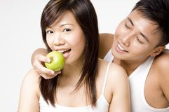 Healthy Couple 3. An attractive male model feeds a pretty young asian woman an apple Royalty Free Stock Images