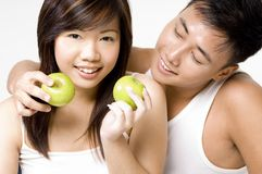 Healthy Couple 4. A healthy good-looking asian couple eating apples. Wearing white on white background Stock Photo