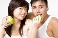 Healthy Couple 5. A healthy-looking attractive asian couple in white eating apples Stock Image