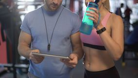Healthy couple discussing workout plan in gym, defining future fitness goals. Stock footage stock footage