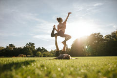 Healthy couple doing acro yoga on grass Royalty Free Stock Photo