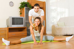 Healthy couple doing fitness. Cheerful healthy couple doing fitness on the mat Royalty Free Stock Image