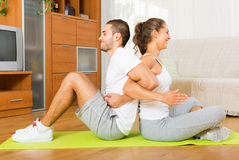 Healthy couple doing fitness. Young healthy couple doing fitness on mat and smiling Royalty Free Stock Photo