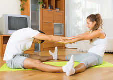 Healthy couple doing fitness. Young men and women doing fitness on a mat and smiling Royalty Free Stock Image