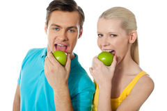 Healthy couple eating fresh green apple. Healthy couple having fresh green apple together Royalty Free Stock Photo