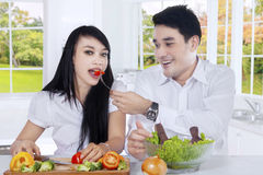 Healthy couple enjoy salad at home. Portrait of healthy couple making vegetable salad and enjoy it together in the kitchen Royalty Free Stock Photo