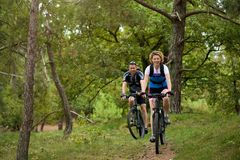 Healthy couple enjoying a bike ride in nature. Portrait of a healthy couple enjoying a bike ride in nature Stock Photo