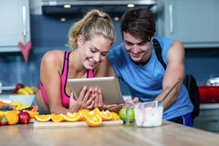 Healthy couple looking at tablet stock images
