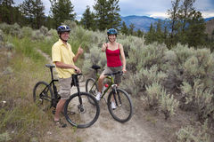 Healthy Couple with Mtn Bikes. Outdoor photo of young adult couple on bicycles on a trail in the mountains Royalty Free Stock Photography