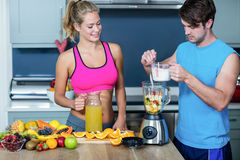 Healthy couple preparing a smoothie Stock Photos