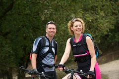 Healthy couple smiling with bicycles. Portrait of a healthy couple smiling with bicycles Stock Image