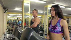 Healthy couple training on a treadmill in a sport centre. A healthy lifestyle stock video footage